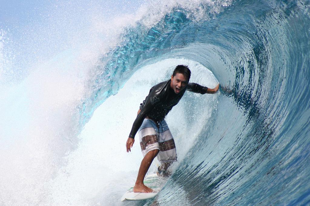 Dennis Tihara riding a wave at Teahupoo, Tahiti.
