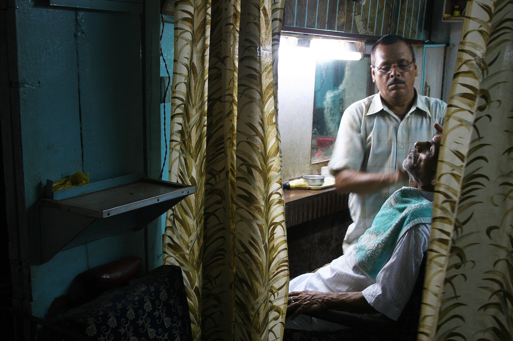 A man getting a shave at a local barber shop in Varanasi, India.