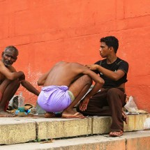 "Man shaving his hair on the Ghats before taking a ""holy dip"" in the Ganges."