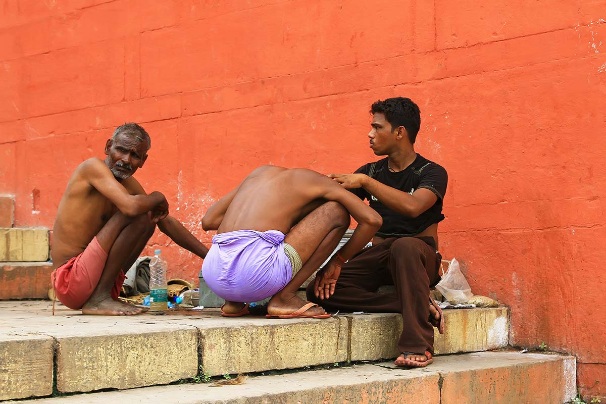 "Man shaving his hair on the Ghats before taking a ""holy dip"" in the Ganges. Shaving the head before visiting the Ganges is thought to bring spiritual purification."