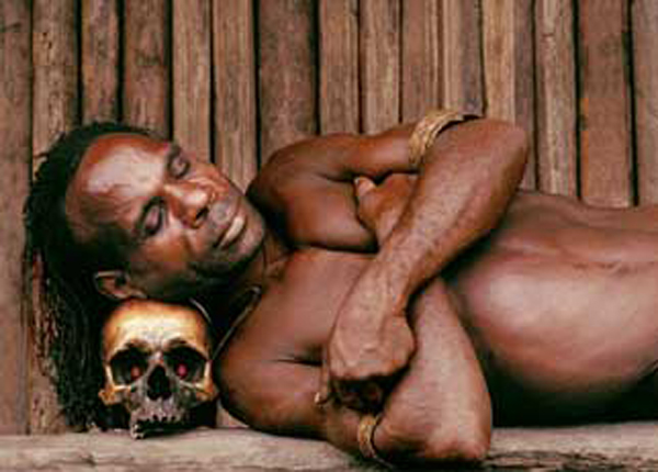 An Asmat tribal man sleeping on a human skull. Photo credit unknown.