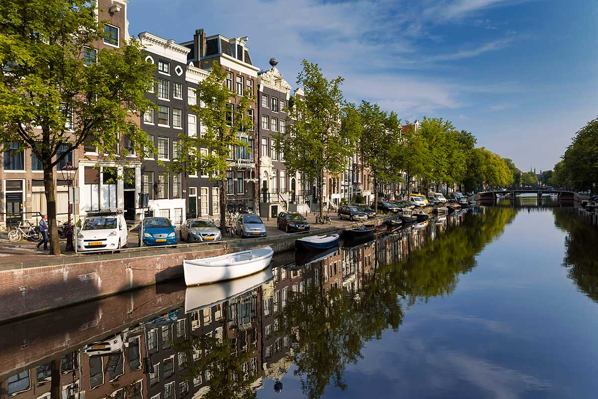 Walking along the canals in Amsterdam is especially cool in the morning. Then you'll get the chance to see the beautiful reflections.
