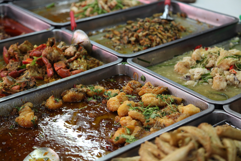 Different varieties of food/curry at a food vendor in Bangkok.
