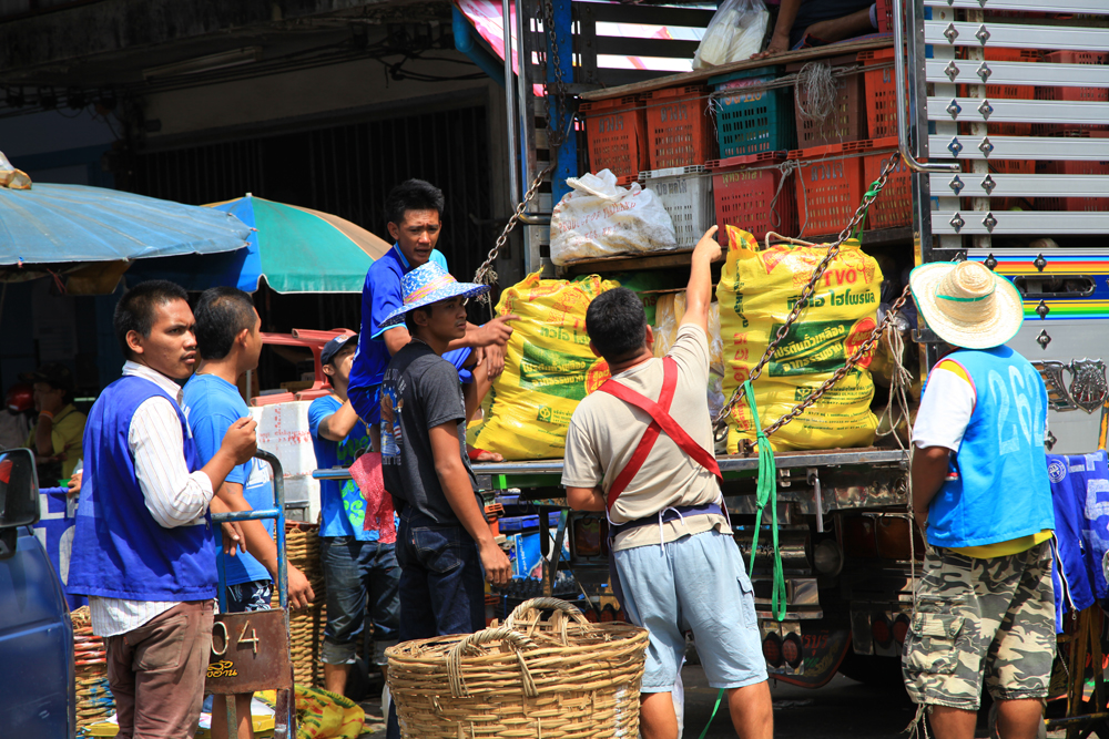 Porters roam the streets of Khlong Toey fresh market, waiting for customers to uploading their latest purchases.