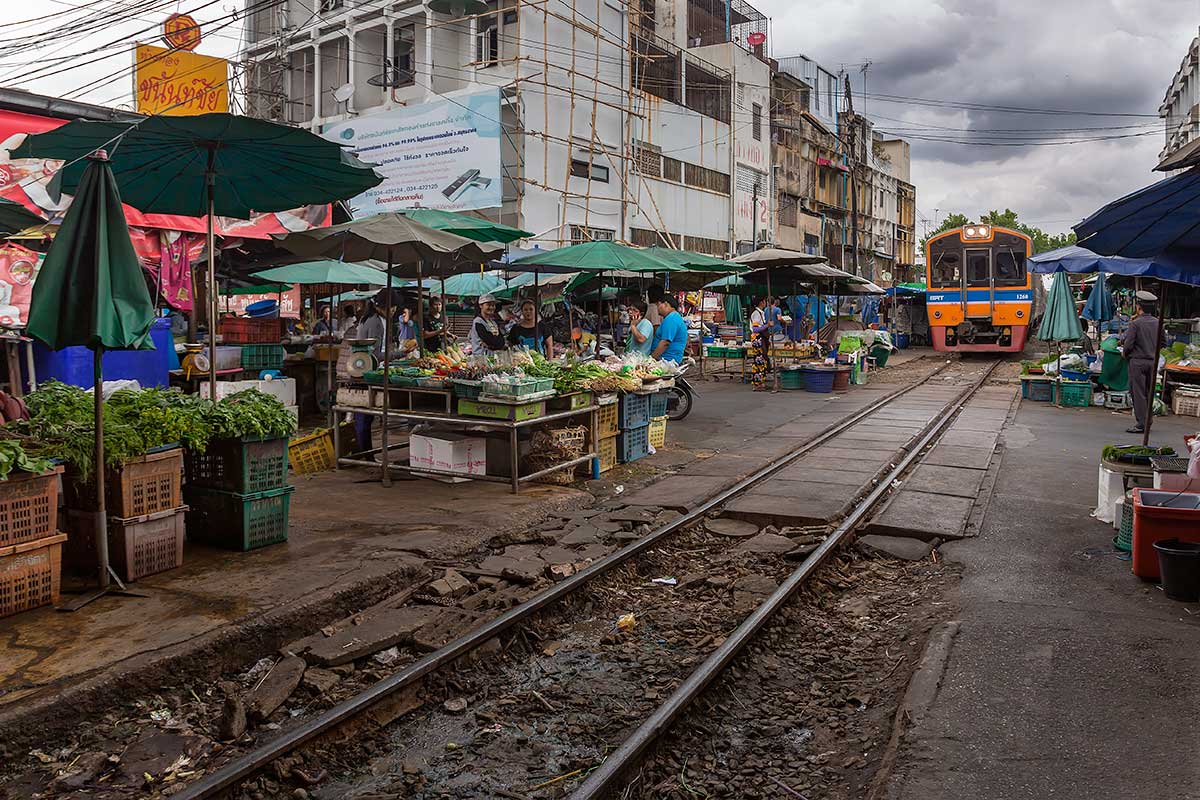 Mahachai market and the railway live next to each other, so when the first train arrives from Bangkok, vendors have to move their wares off the tracks for the train to pull into the station.