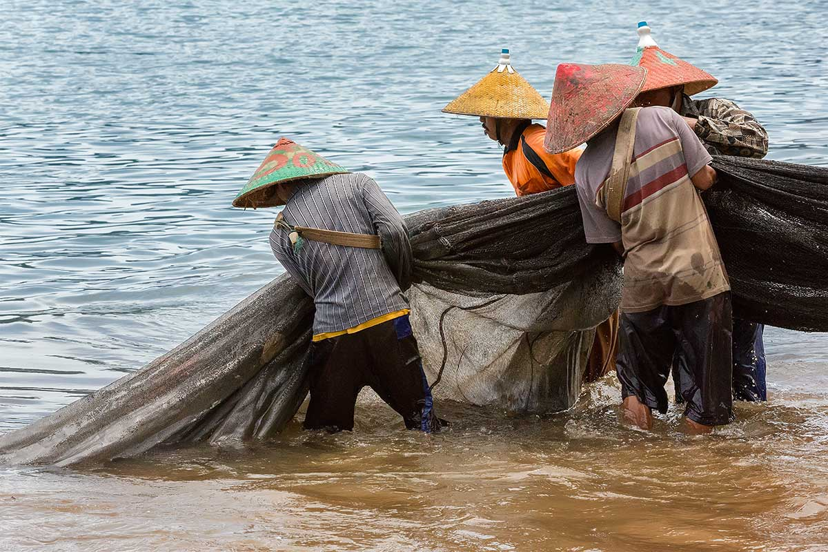 Fishermen pulling in a catch at Bungus beach in Sumatra.