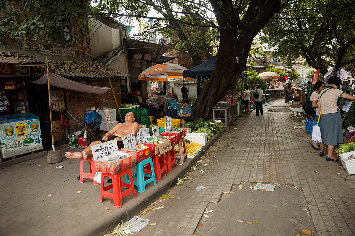 A typical street scene in Guangzhou: A street vendor sleeping at Huayuan market.