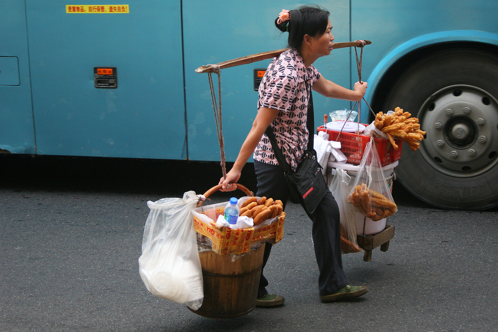 Woman selling small snacks at the Guangzhou railway station.