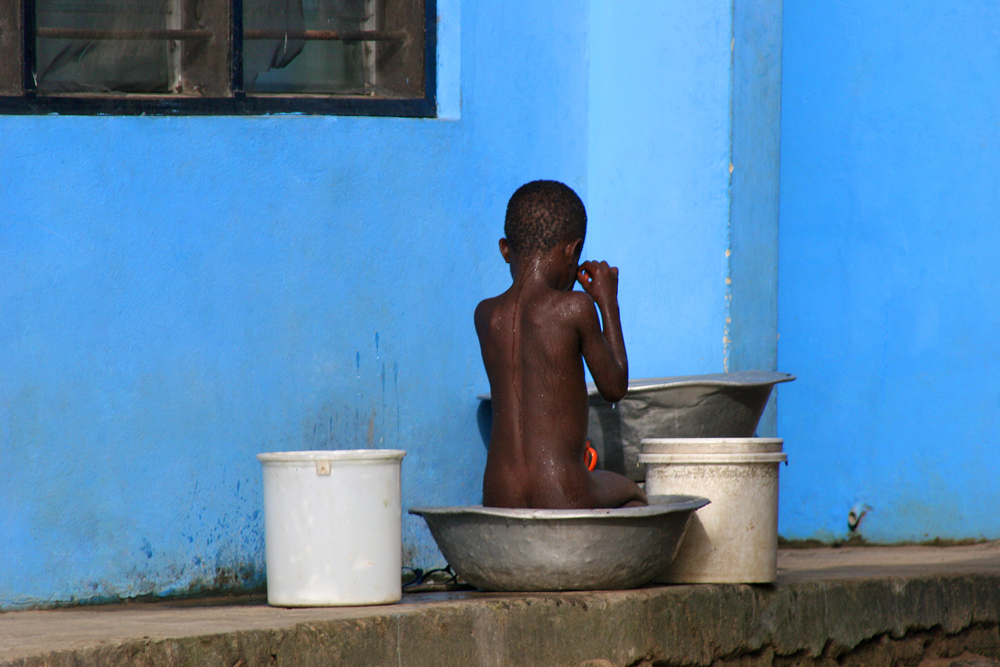 Blue - Boy and the blue wall in Accra, Ghana.