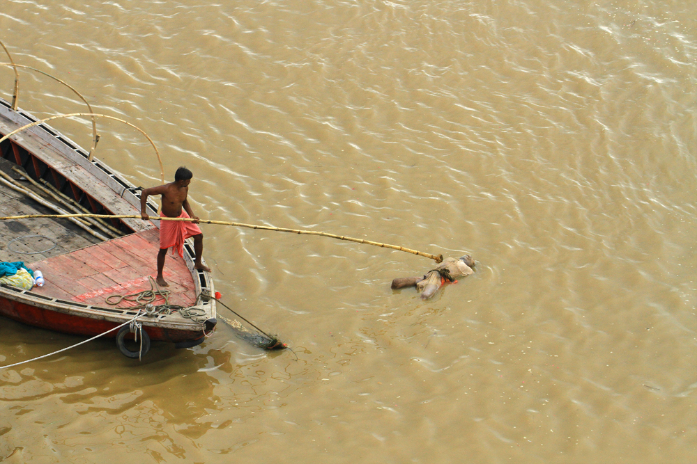 Dead body floating by in Varanasi, India.