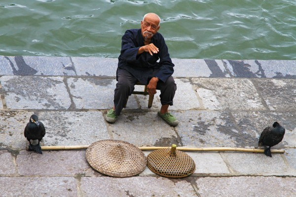 A fisherman with his Cormorant waiting for customers.