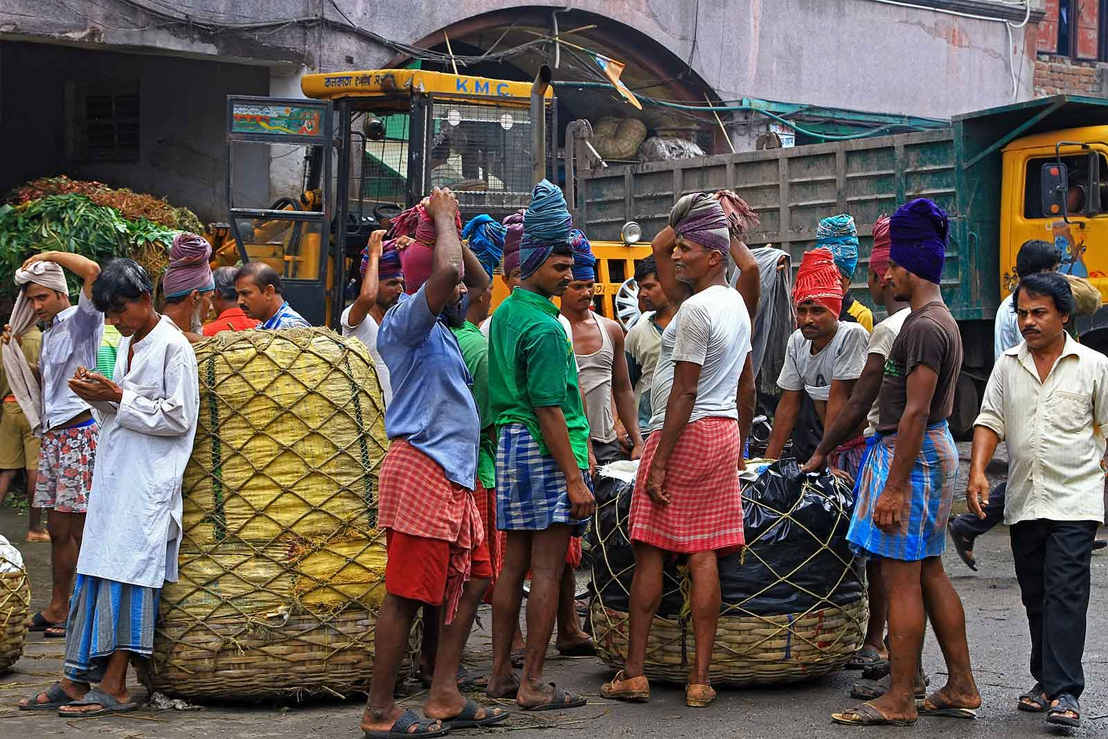 Getting ready to lift up a heavy pile of vegetables in Kolkata, India.