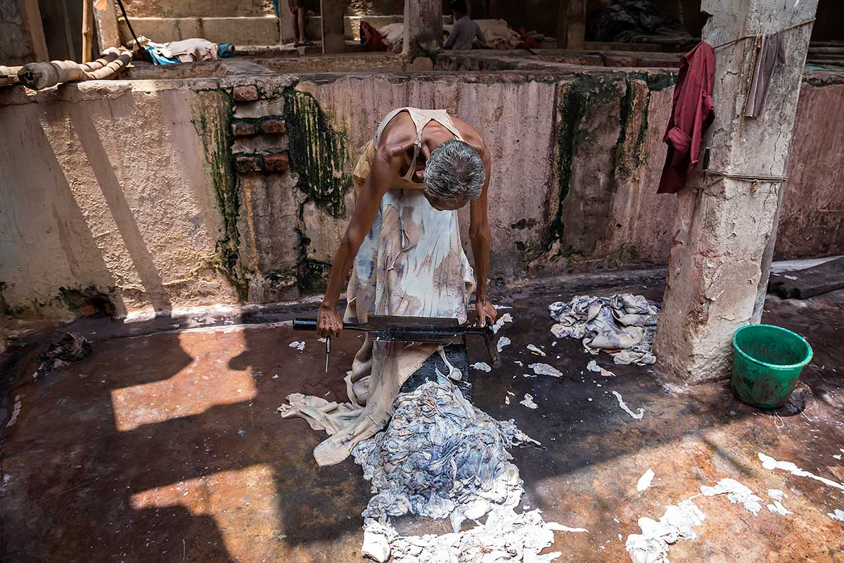 A man scrapes the inside of a cow skin to remove small parts to make it smoother. He uses a special designed sharp tool.