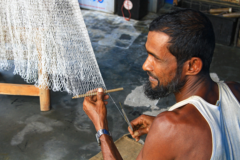 Producing fishing nets by hand in Kuakata, Bangladesh.