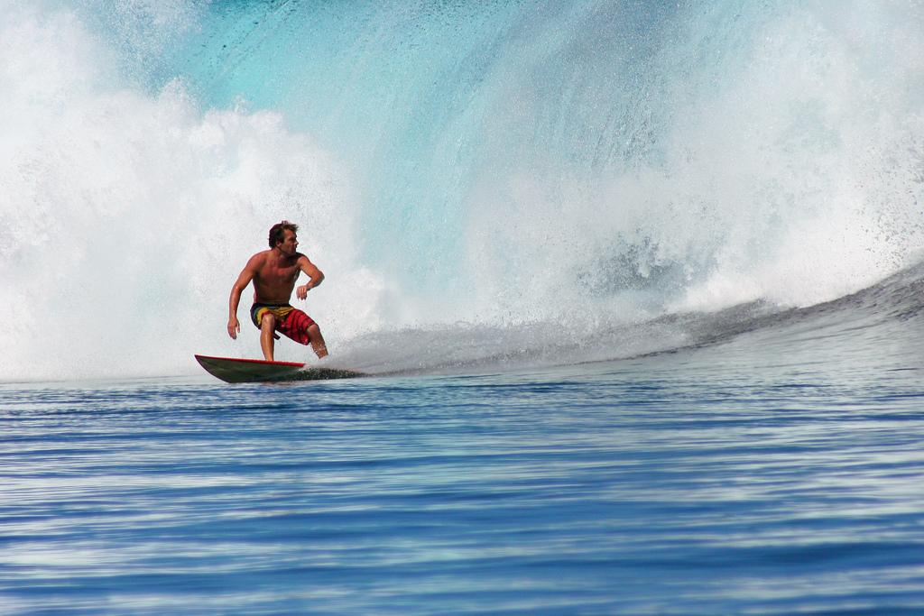 A surfer conquering the waves at Teahupoo, Tahiti.