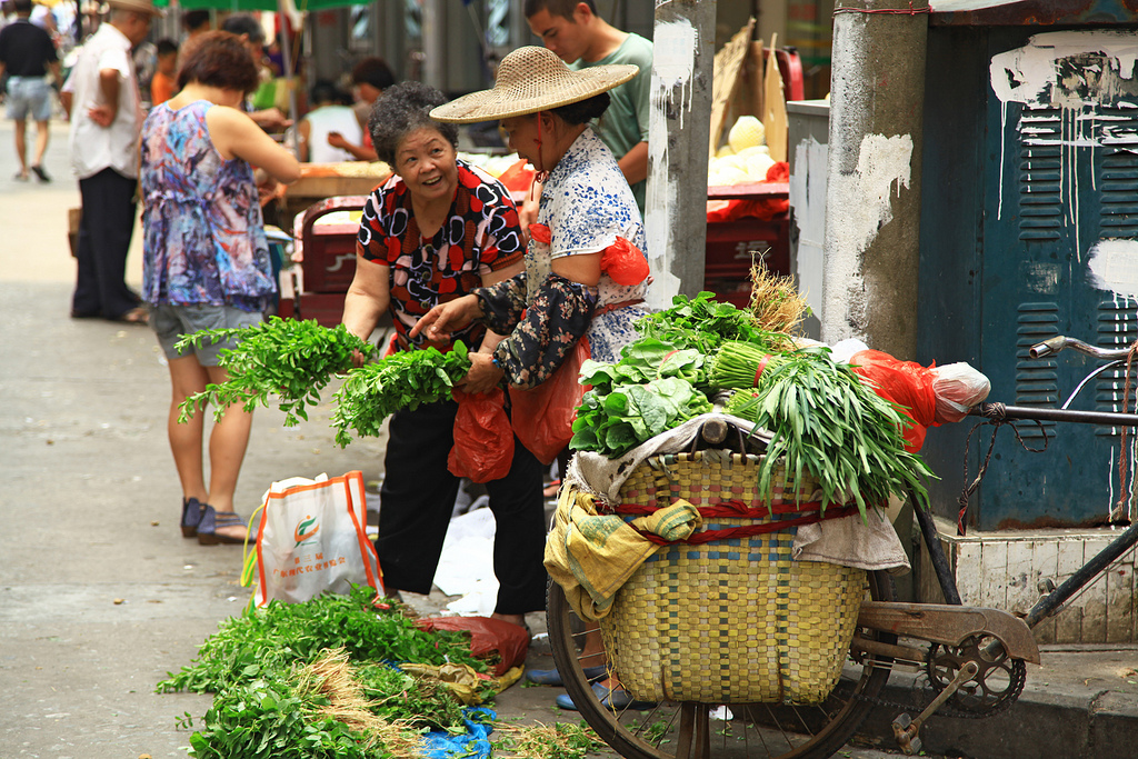 Women selling goods at a market in Guangzhou, China.