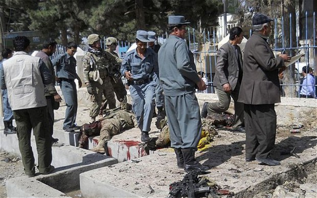 Afghan policemen and NATO troops inspect the site of a suicide attack in Faryab province, Afghanistan. Photo: REUTERS
