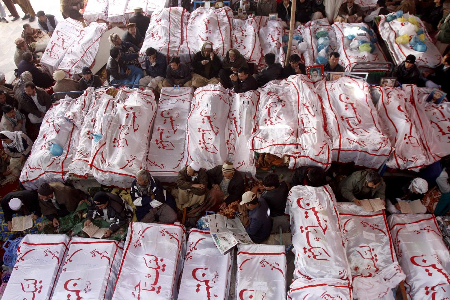 Associated Press/Arshad Butt - Pakistani Shiite Muslims sit in protest next to the dead bodies of their family members killed in Saturday's bombing