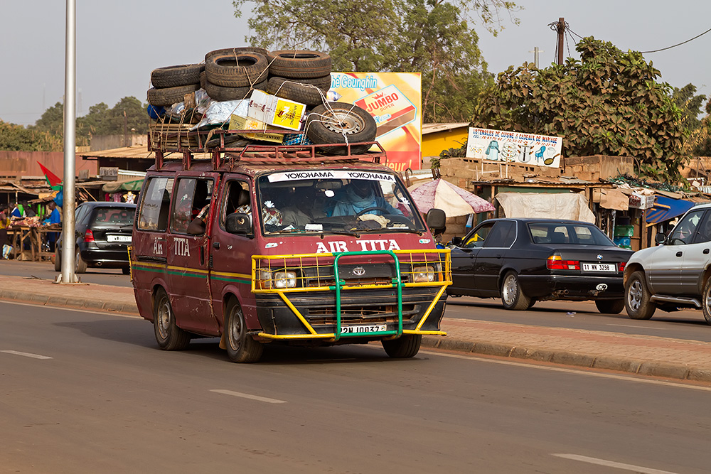 Fully loaded bush taxi in Ouagadougou, Burkina Faso - A couple of tyres in tow to be on the safe side...