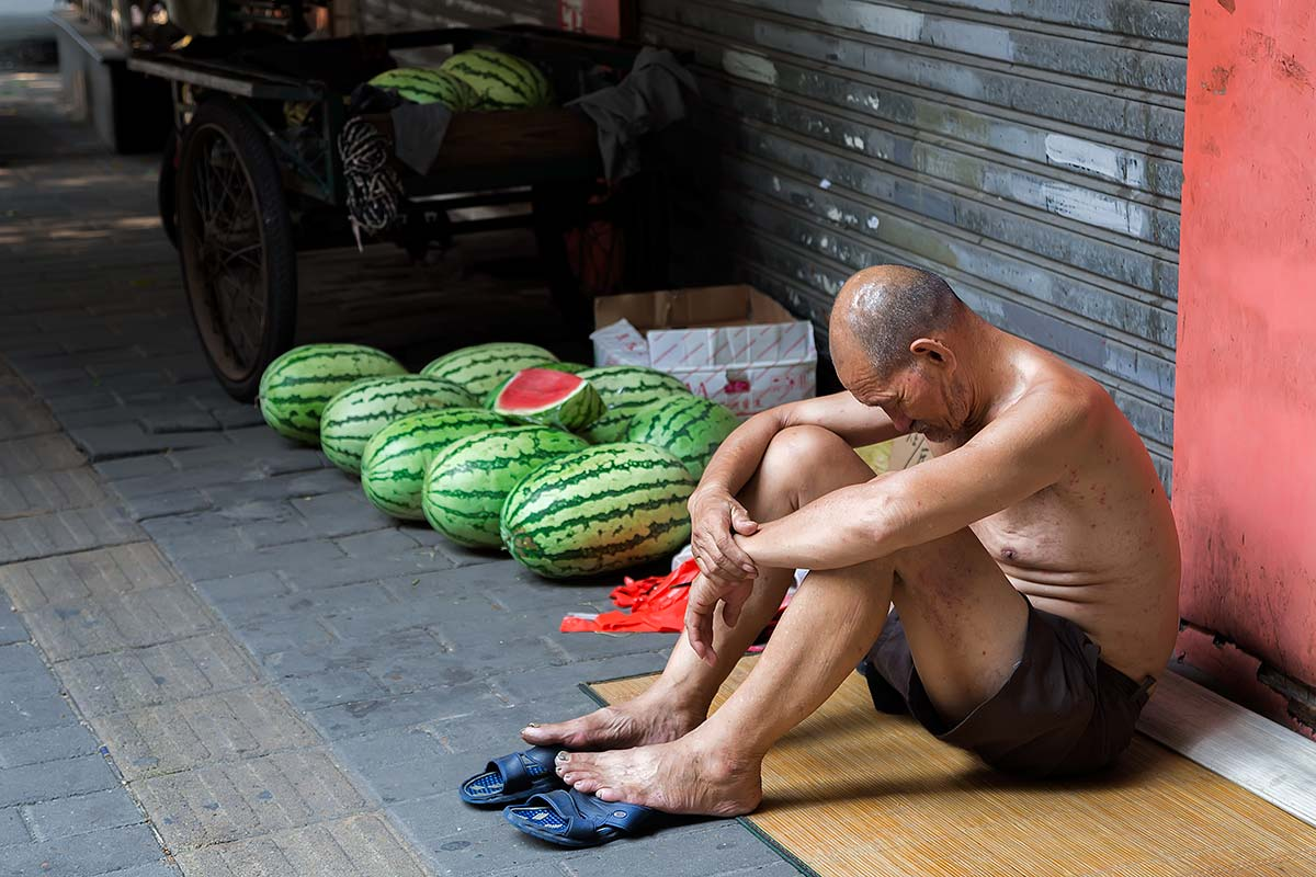 Shirtless Chinese selling watermelons in the streets of Beijing.