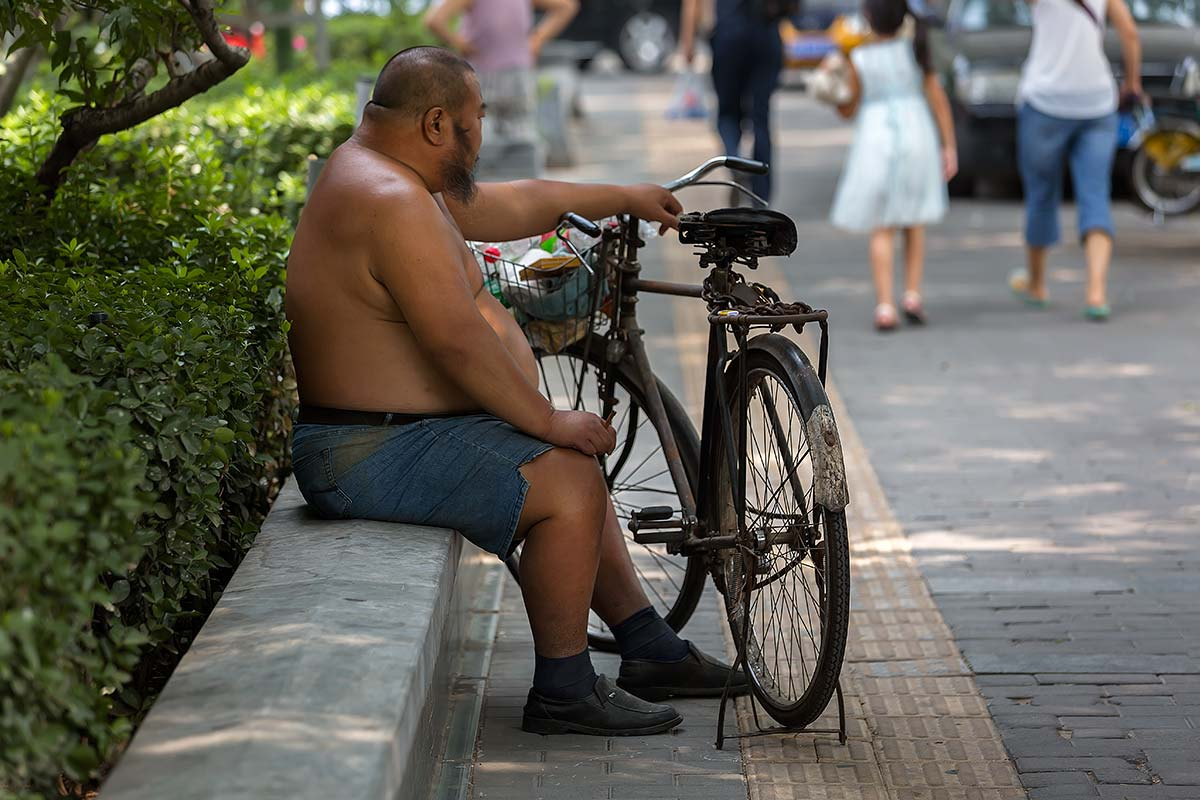 Shirtless Chinese sitting in the streets of Guangzhou.