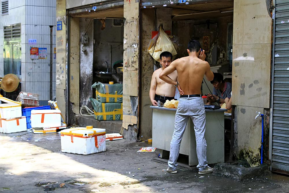 Chinese men without their T-Shirts in the middle of the street in Guangzhou, China.