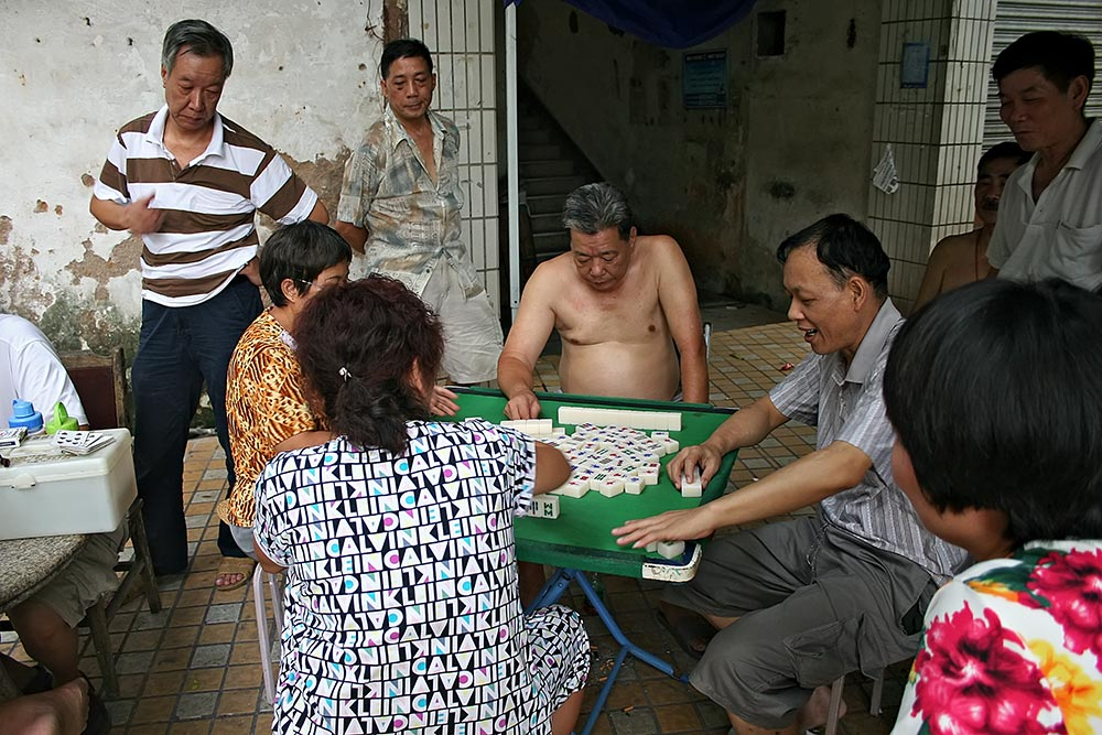 Shirtless Chinese man playing a game of Mahjong in Guangzhou.