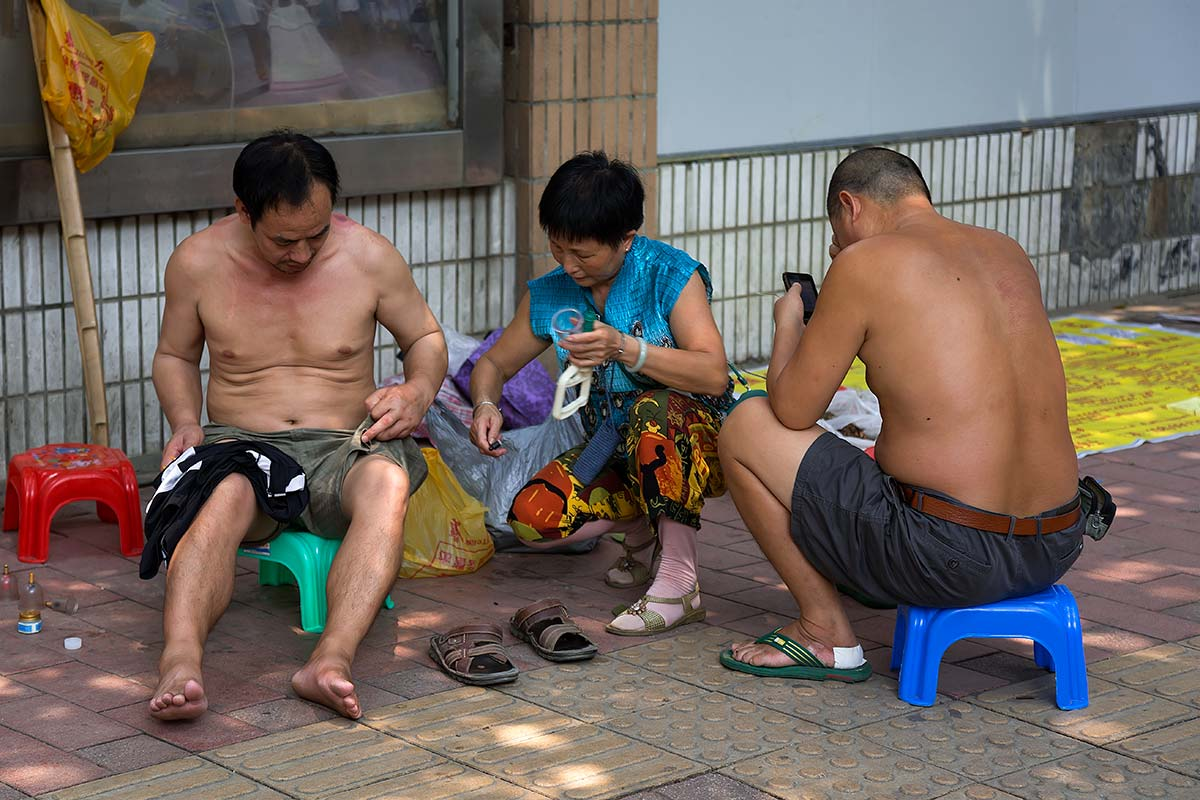Shirtless Chinese men in the streets of Beijing.