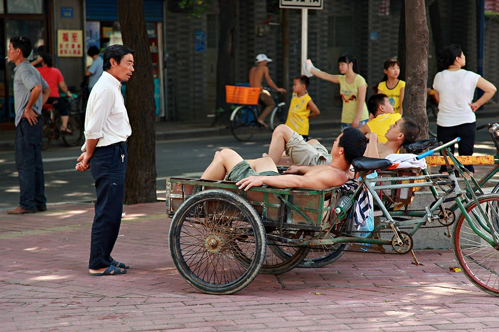 Shirtless men resting in the streets of Guangzhou, China.