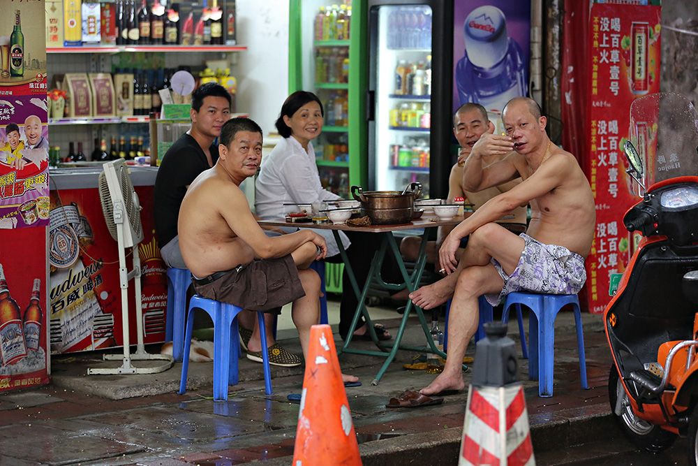Shirtless men eating dinner in the streets of Guangzhou, China.