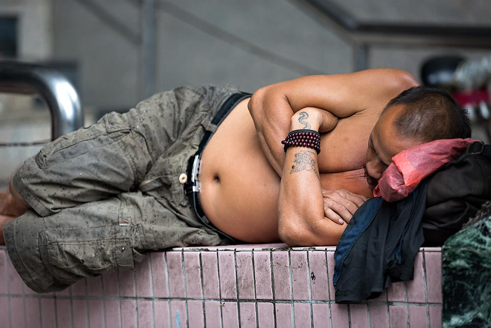 Shirtless Chinese man sleeping in the streets of Guangzhou.