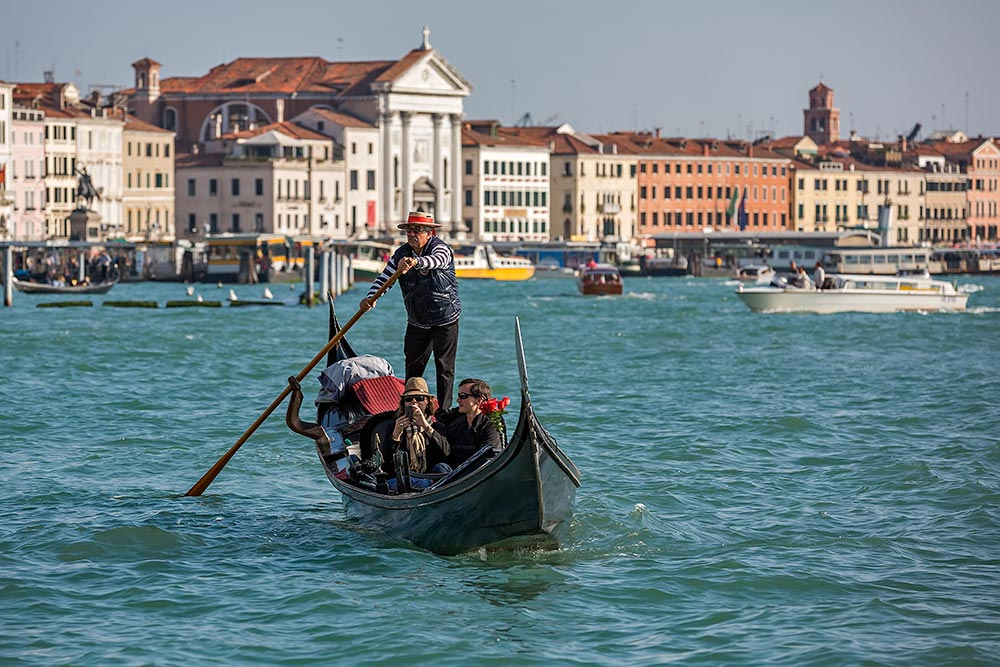 For centuries gondolas were the chief means of transportation and most common watercraft within Venice. It's driven by a gondolier. In modern times the iconic boats still have a role in public transport in the city, serving as ferries over the Grand Canal.
