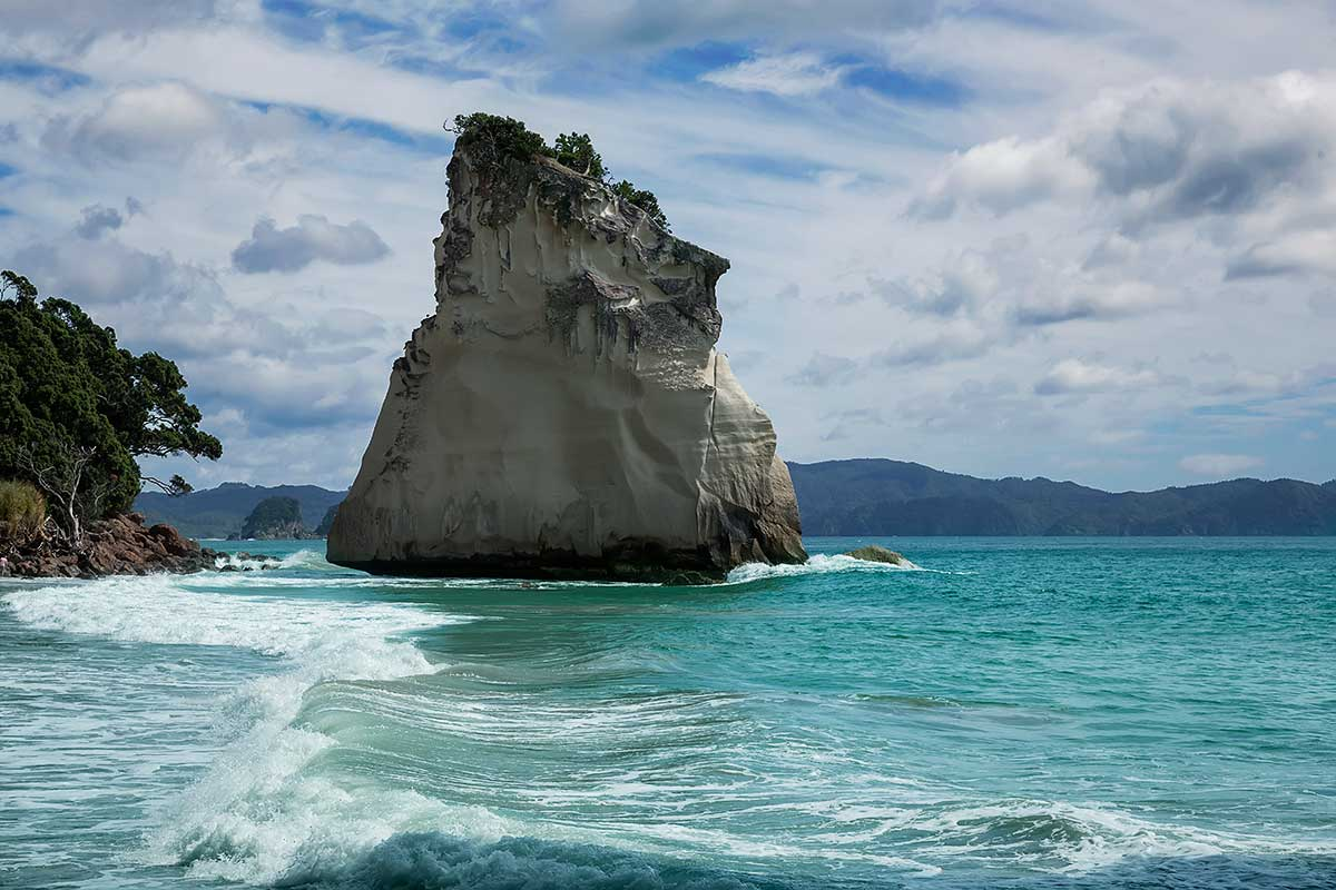 The striking rock known as 'Te Hoho'. Just off the beach at Cathedral Cove is a large pinnacle of pumice breccia. Over centuries this has been sculpted by wind and water - it now looks like the prow of a large ship steaming into the beach.