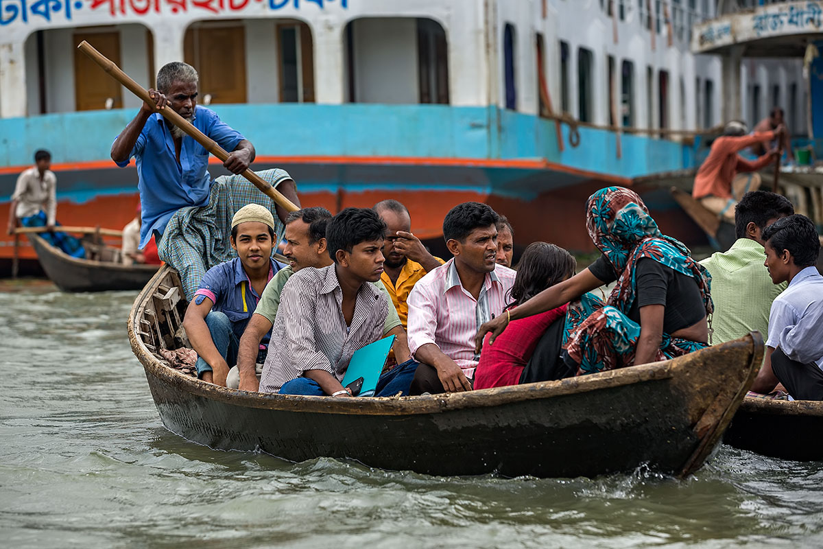 A ferryman taking people across the Buriganga River in his wooden boat. The Buriganga river is one of the most dangerous waterways on Earth, especially for the ferrymen.