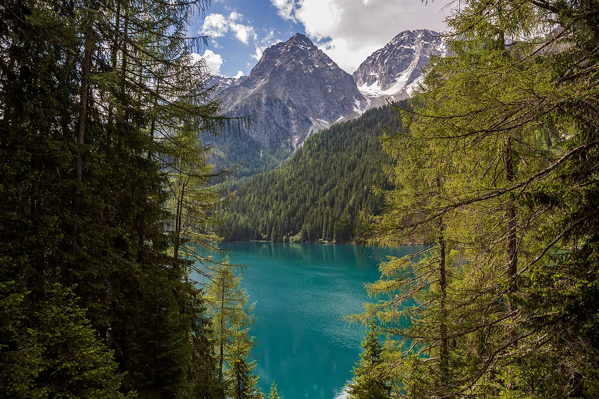 Mountains and blue water at the Antholzer See in South Tyrol, Italy.