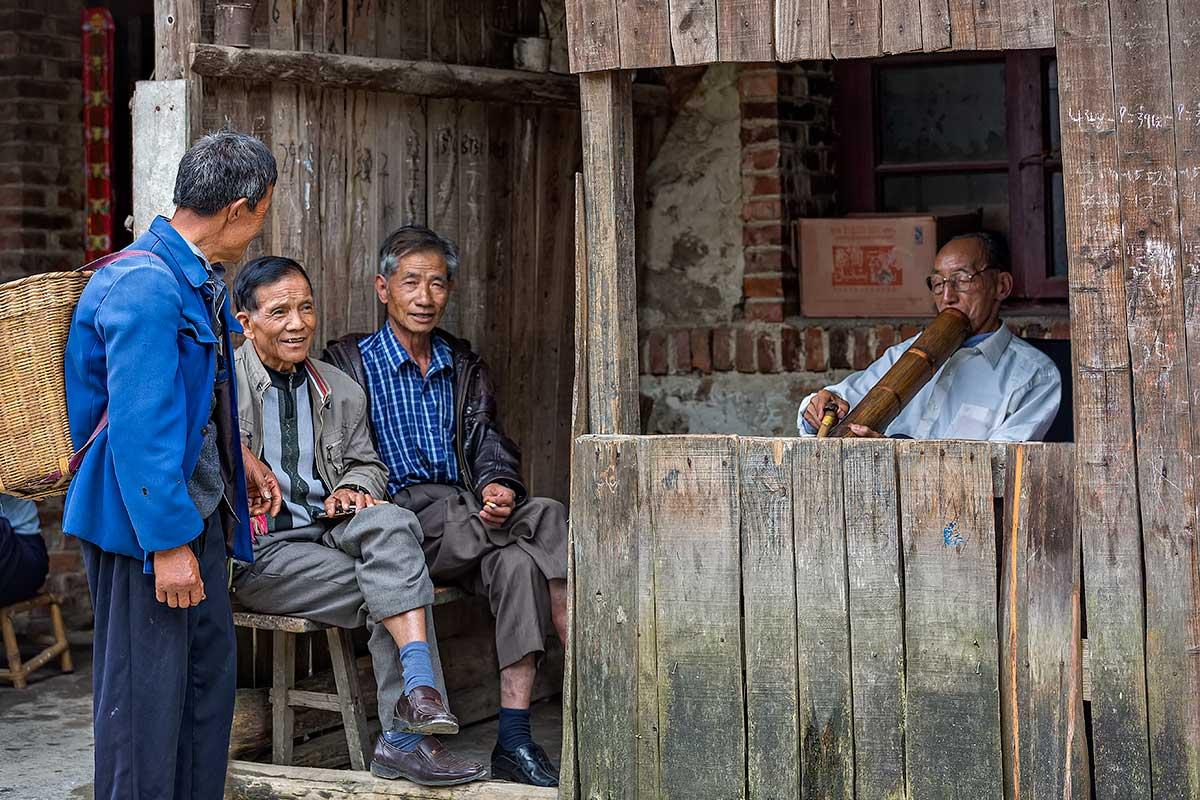 Men smoking a pipe in Xinjie, Yunnan Province, China.