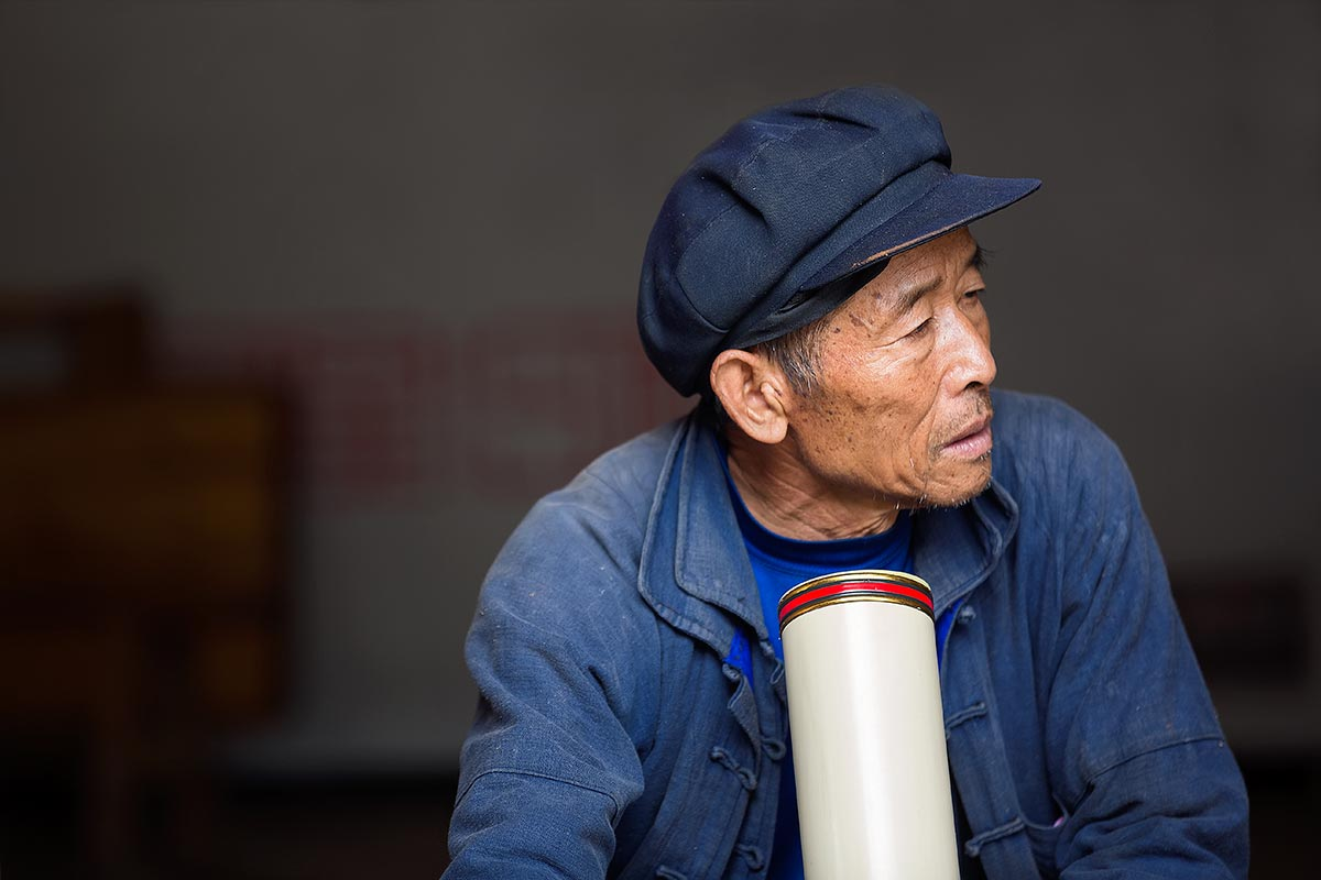 A local Chinese smoking a pipe in the old town of Xinjie.