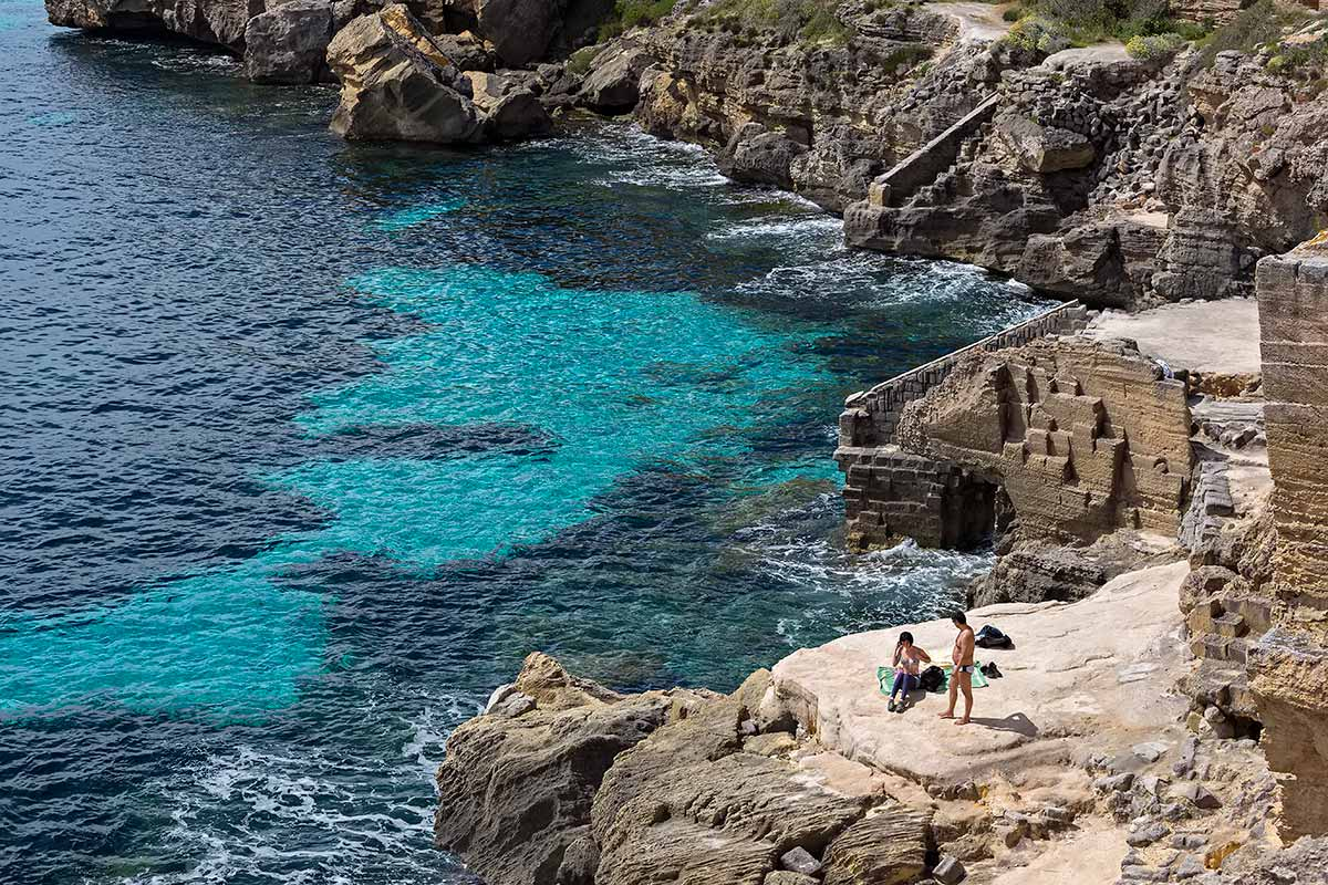 It's quite a scramble to get down the rocks of Cala Rossa beach, but determined holiday-makers don't this obstacle keep them from it.