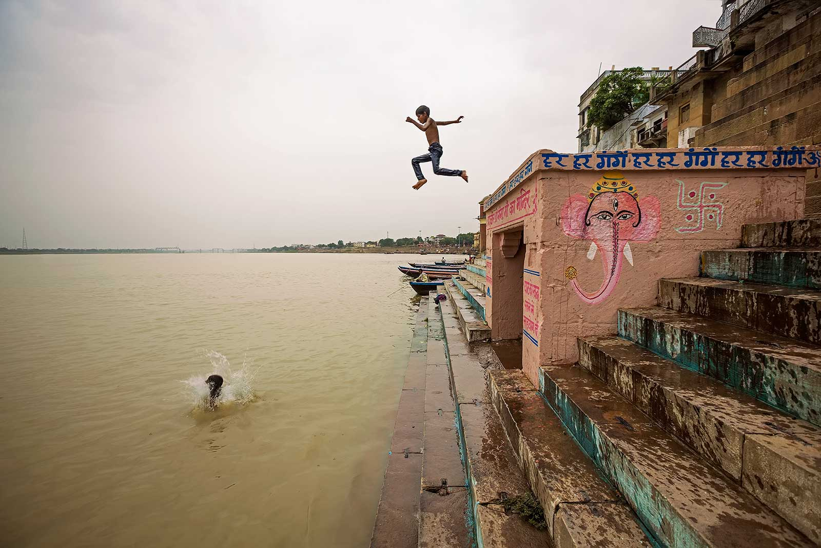 Kids jumping into the Ganges river while walking along the Ghats in Varanasi.