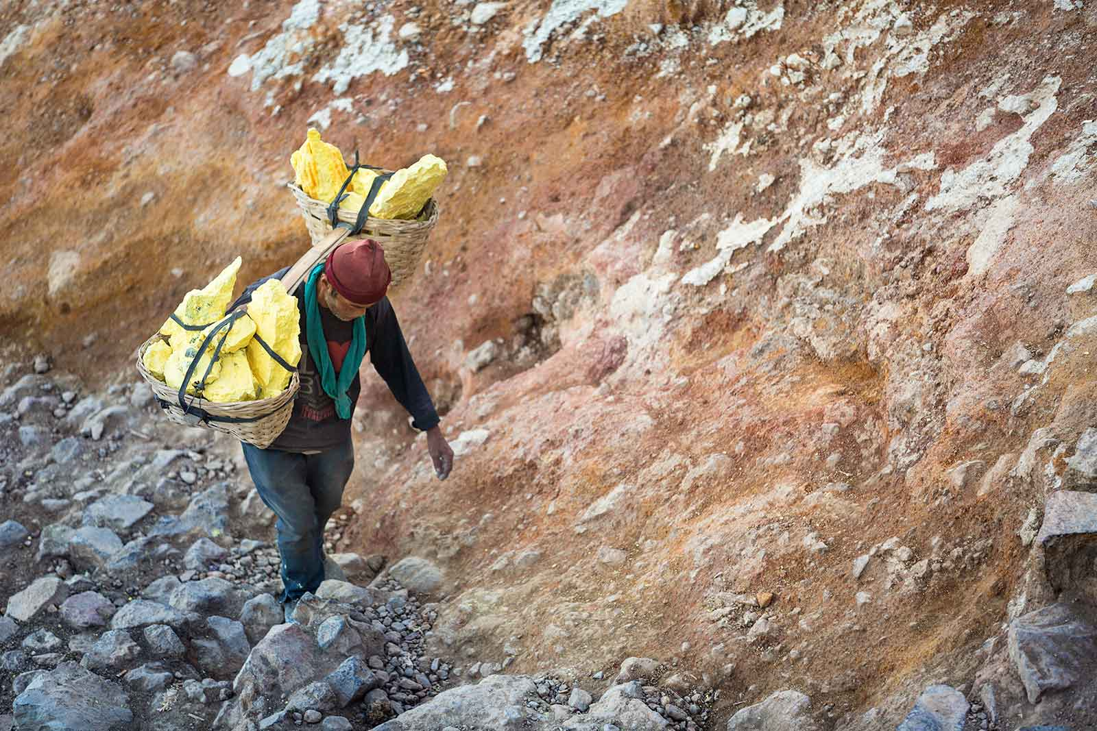A miner ascends from the Kawah Ijen crater with his baskets full of sulfur.