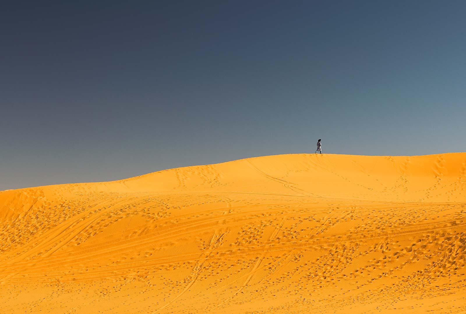 A berber walks along the sand dunes of Erg Chebbi.
