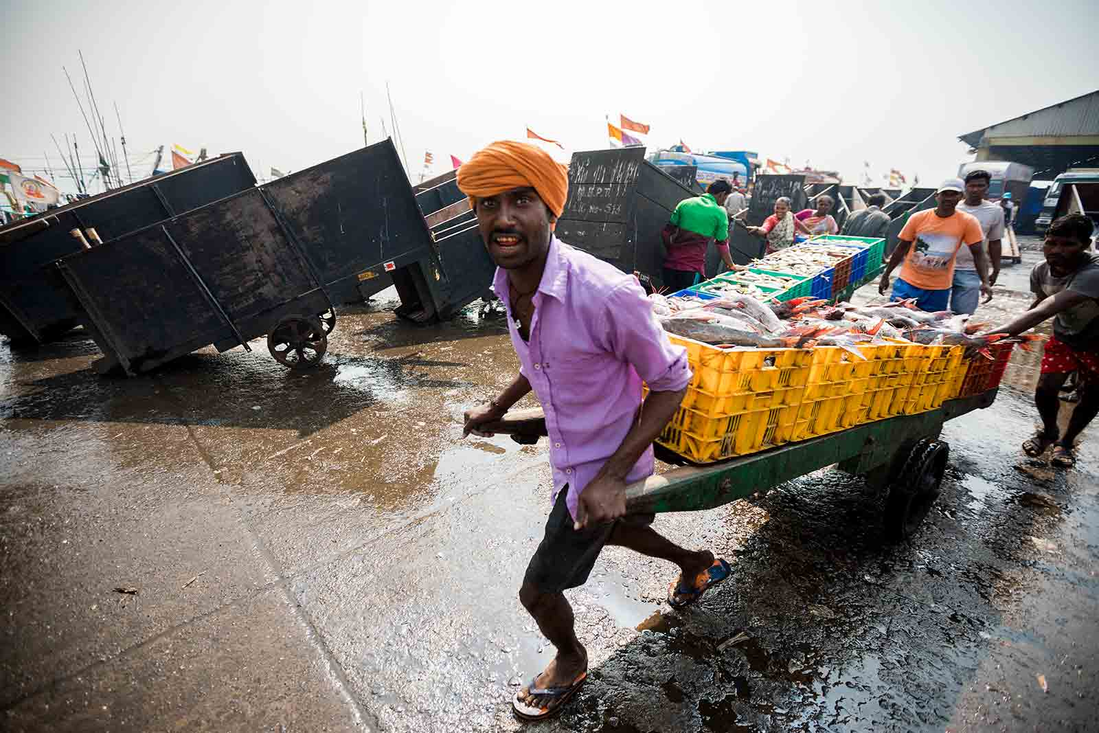 Men push loaded handcarts through the crowds at Sassoon Docks as they yell for people to get out of the way.