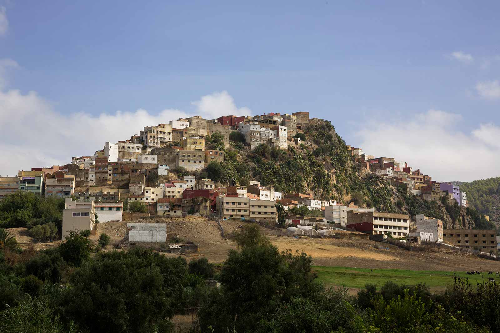 Moulay Idriss is reachable by just a pair of roads and spreads across two foothills of Mount Zerhoun, at the base of the Atlas Mountains.
